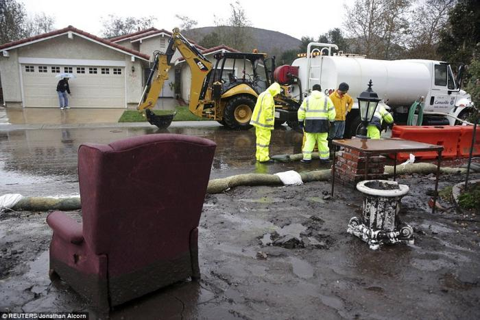A chair is seen in a damaged front yard as crews work to channel mudflows in the area of the 2013 Sp