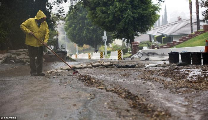 A resident sweeps water and debris as rain begins to fall in Glendora, California as a major Pacific