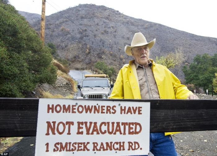 Resident Tom Smisek stands at a warning sign in Silverado Canyon, California on Tuesday.