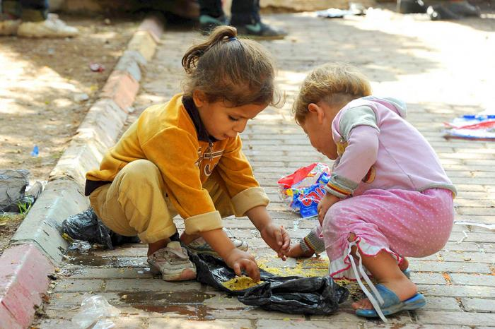 Children feast on crumbs harvested from a gutter, revealing just how desperate many of the people ar