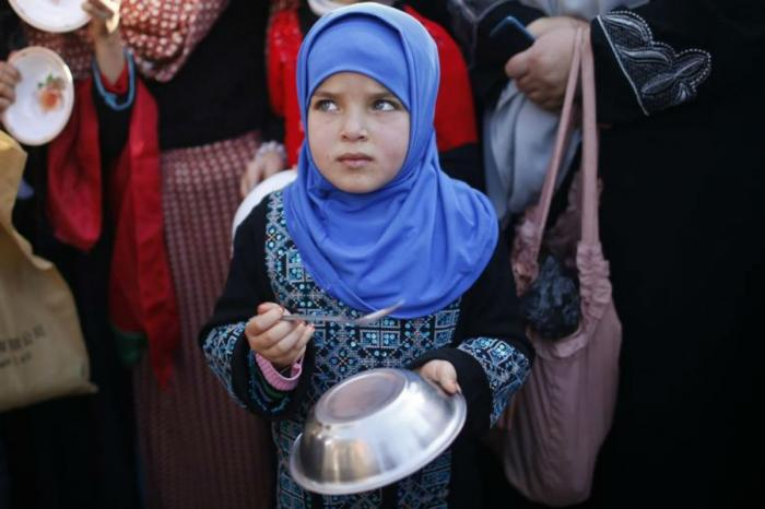 A girl waits for food distribution along with thousands of other hungry refugees. Her future, along