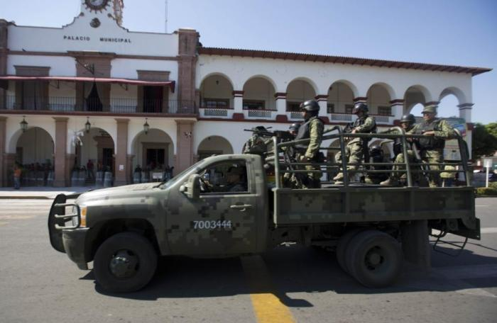 Soldiers patrol City Hall in Apatzingan, Mexico, last year during tense standoff with vigilantes.
